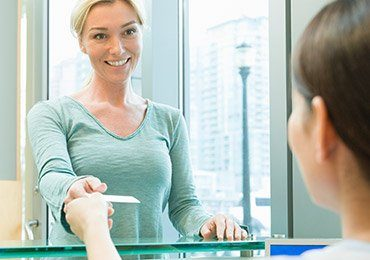 Smiling woman checking in at reception desk