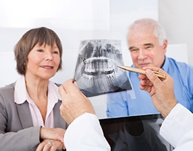 Dentist explaining cost of dental implants in Chesterfield with X-ray.