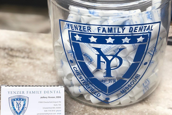 Yenzer family dental logo on jar with lip balm