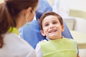 boy smiling sitting in children's dentist chair