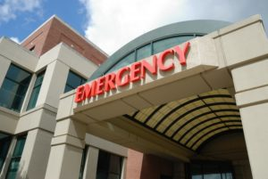 Entry archway to an emergency room with red letters spelling emergency