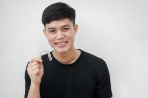 young man smiling while holding Invisalign in Chesterfield