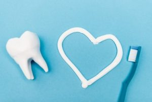 A tooth, a heart drawn with toothpaste and a blue toothbrush laying against a light blue background