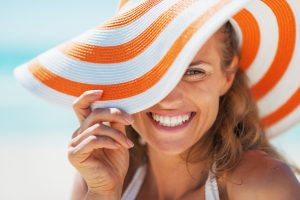 happy young woman in swimsuit and beach hat